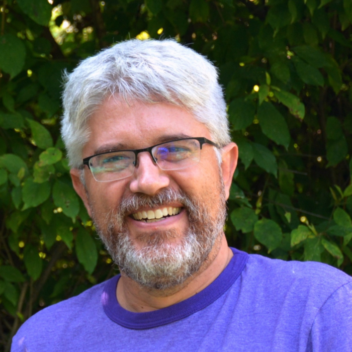Doug Kaufman smiles at the camera in front of greenery; his short hair and beard are white and he wears rectangle glasses.